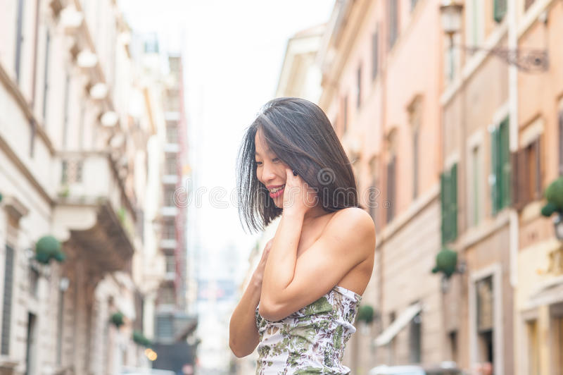 微笑使用手机春天ur的年轻美丽的亚裔妇女 库存图片
