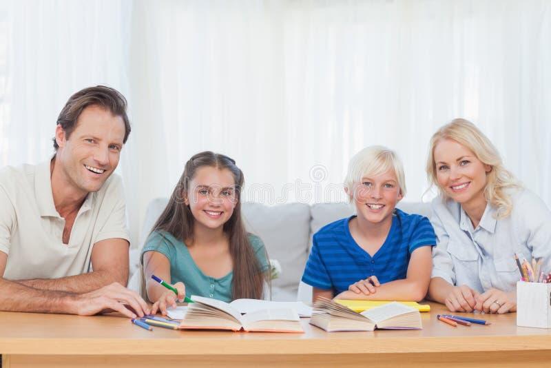 微笑做父母帮助他们的有他们的家庭作业的孩子 图库摄影