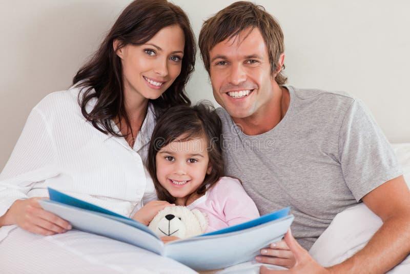 微笑做父母读故事给他们的女儿 图库摄影