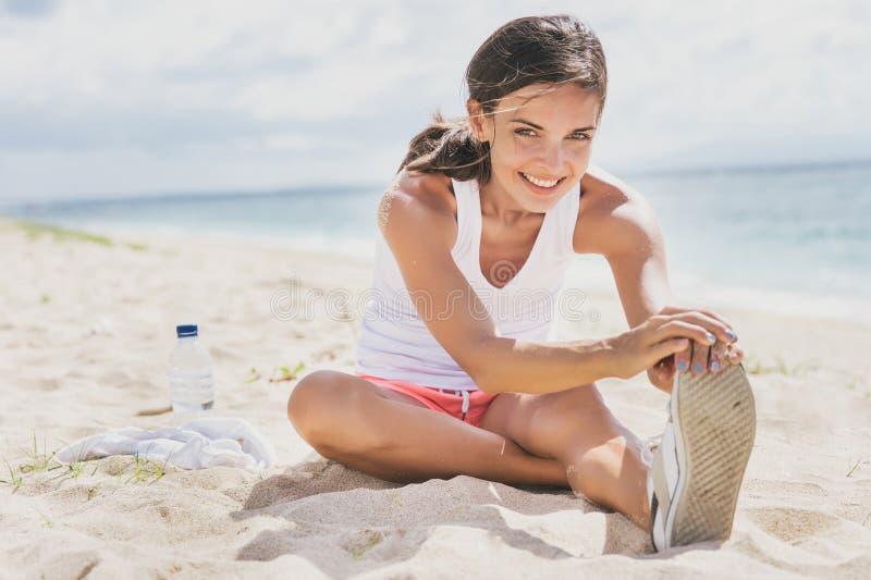 微笑健康的妇女,当做腿舒展时 库存图片
