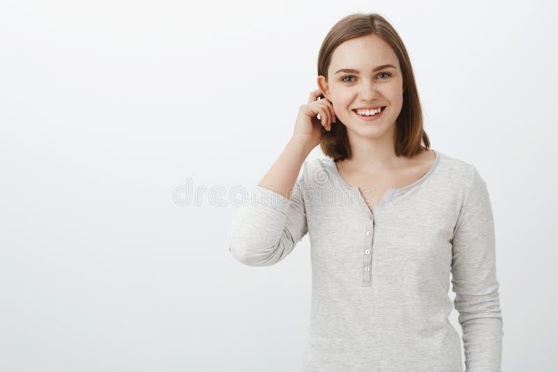 微笑偶然的女衬衫的逗人喜爱的感情十几岁的女孩甩在拍动的耳朵后的头发和广泛地感到害羞和快乐 免版税库存照片