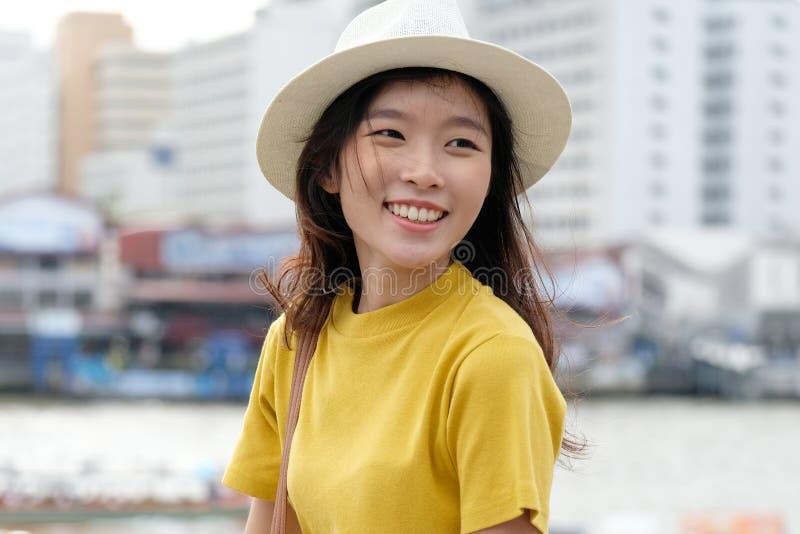 微笑充满幸福的年轻亚洲妇女画象对城市户外背景,愉快的片刻,偶然lifesyle,旅行博客作者 库存图片