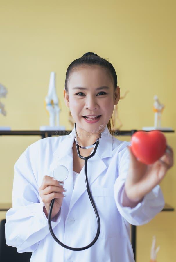 微笑医生亚洲女性的手拿着听诊器和心脏红色模型,愉快和,选择聚焦 免版税库存照片