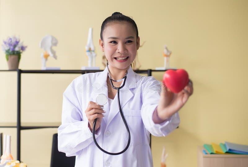 微笑医生亚洲女性的手显示仪器心脏红色模型,愉快和,选择聚焦 库存图片