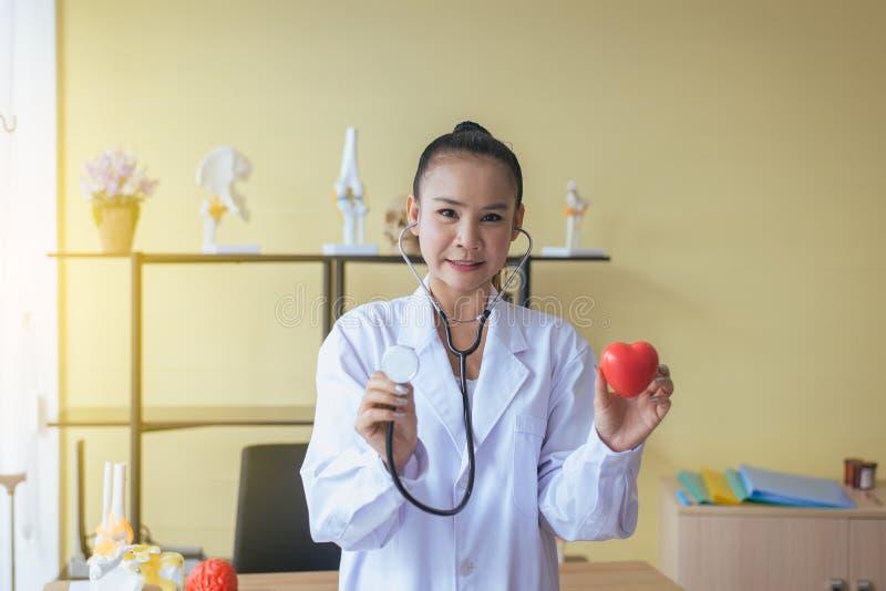 微笑医生亚洲妇女的手显示仪器听诊器和心脏红色模型,愉快和,选择聚焦 免版税图库摄影
