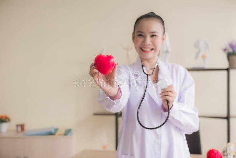 微笑医生亚洲妇女的手显示仪器心脏红色模型,愉快和,选择聚焦 免版税图库摄影