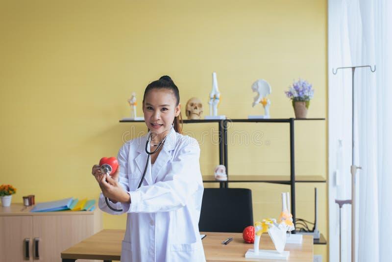 微笑医生亚洲妇女的手显示仪器心脏红色模型,愉快和,选择聚焦 免版税库存照片