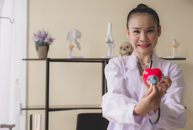微笑医生亚洲妇女的手显示被弄脏的仪器心脏红色模型,愉快和,选择聚焦 免版税库存照片