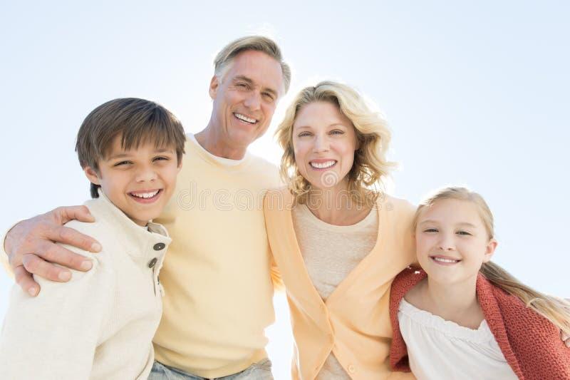 微笑反对清楚的蓝天的孩子和父母 免版税库存照片
