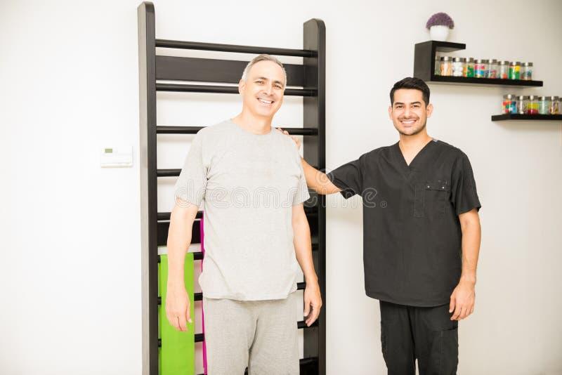 微笑反对肋木的生理治疗师和患者在Hospita 免版税库存图片