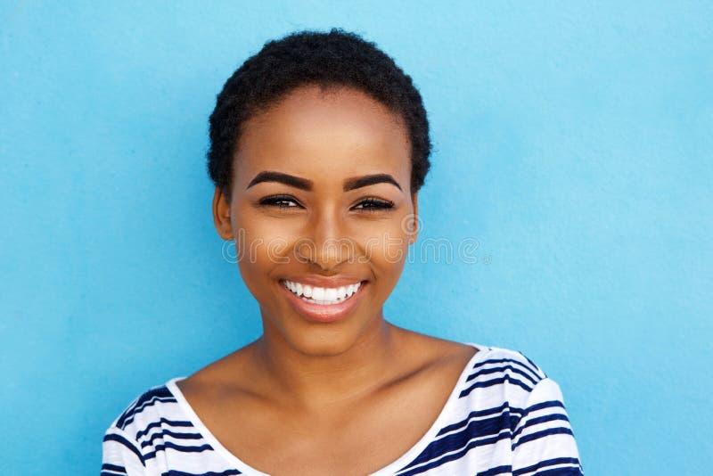 微笑反对蓝色背景的愉快的年轻黑人妇女 库存照片