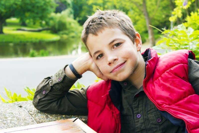 微笑反对绿色背景的十几岁的男孩 免版税库存图片