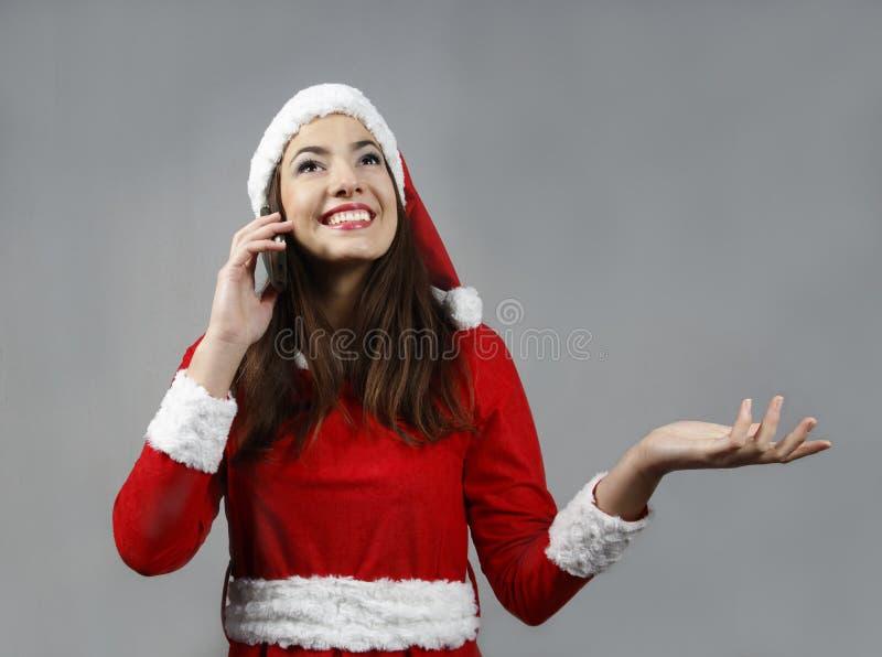 微笑可爱的圣诞老人的女孩和打电话 免版税图库摄影