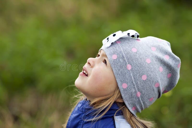 微笑可爱的小女孩摆在被弄脏的背景和  库存图片
