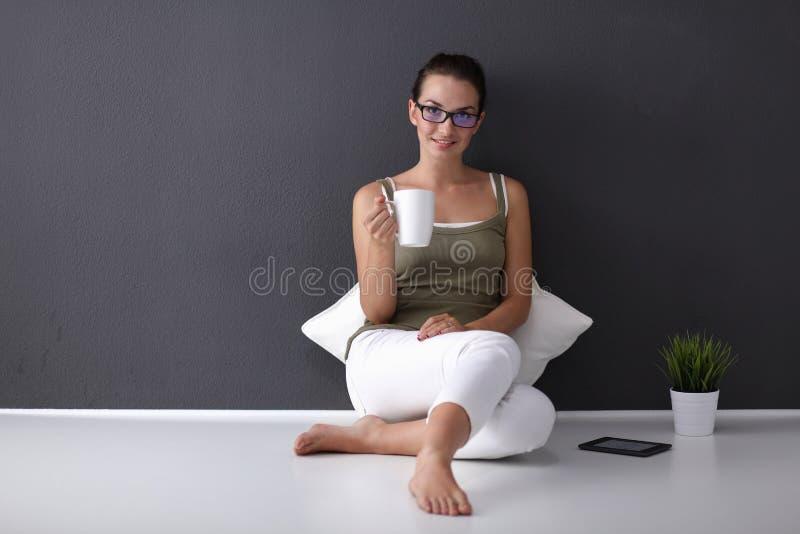 微笑可爱的年轻女人拿着一杯咖啡和,当坐地板时 库存图片