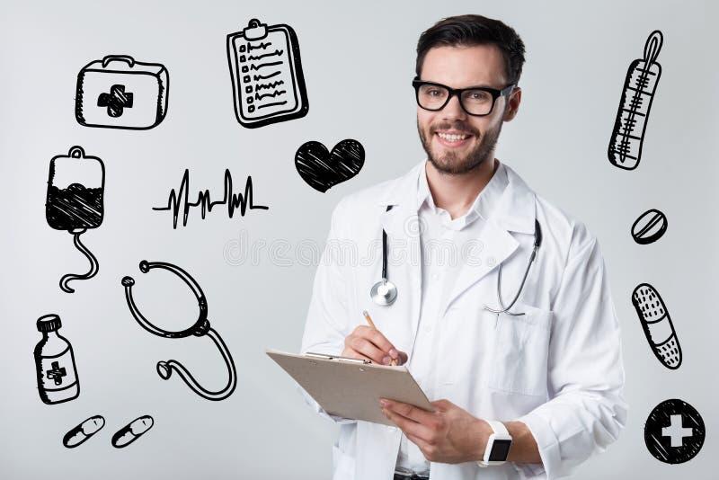 微笑合格的医生,当写处方给他的患者时 库存照片