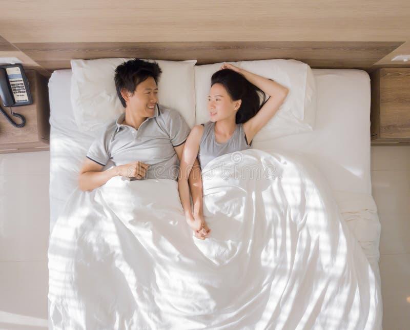 微笑和一起睡觉在爱和性概念的床上的愉快的亚洲夫妇顶视图在有白色的一间现代卧室 库存照片