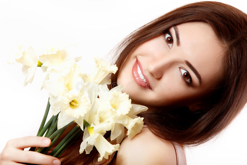 微笑和与花水仙的美丽的青少年的女孩 免版税库存照片