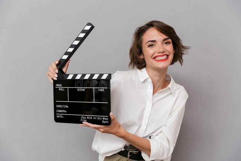 微笑和举行黑clapperbo的白种人妇女20s照片  免版税库存图片