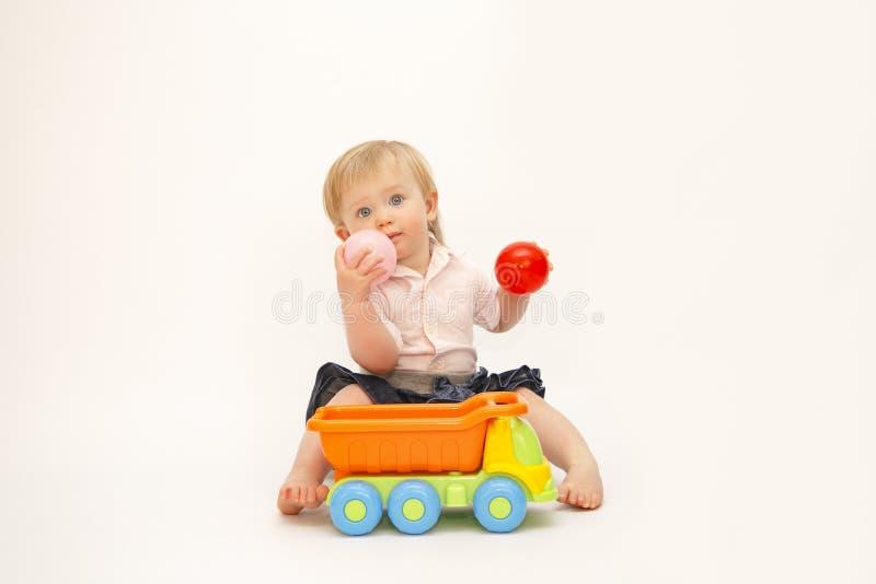 微笑和使用与在白色背景的玩具的小女孩 免版税库存照片