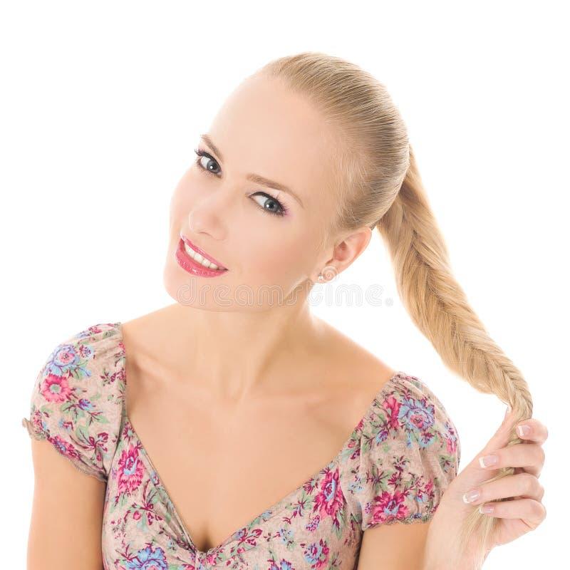 微笑和使用与她的头发/白肤金发的女孩的女孩 免版税图库摄影