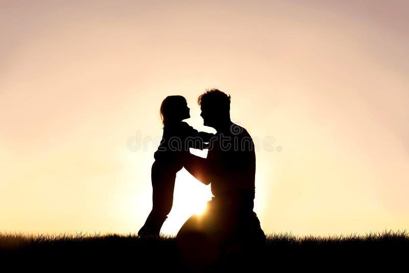 微笑和使用在日落的愉快的父亲和他的小孩剪影  免版税库存图片