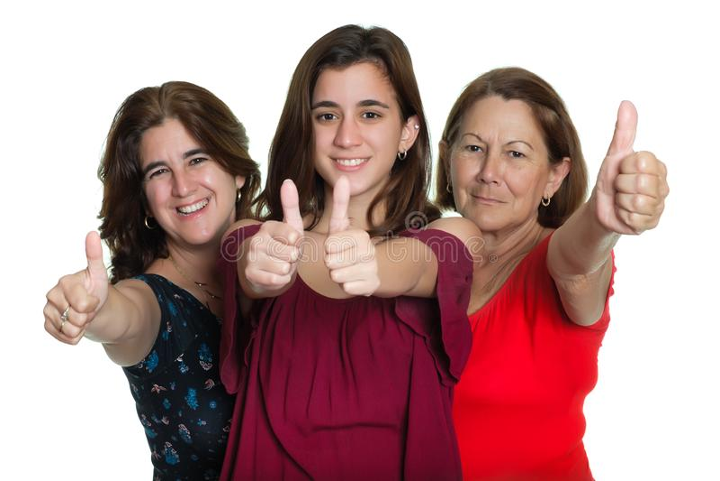 微笑和做赞许标志- -在白色背景的拉丁妇女的三世代 免版税图库摄影