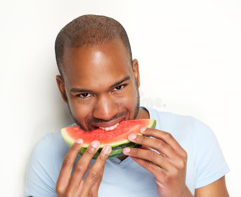 微笑和吃可口西瓜的年轻人 图库摄影