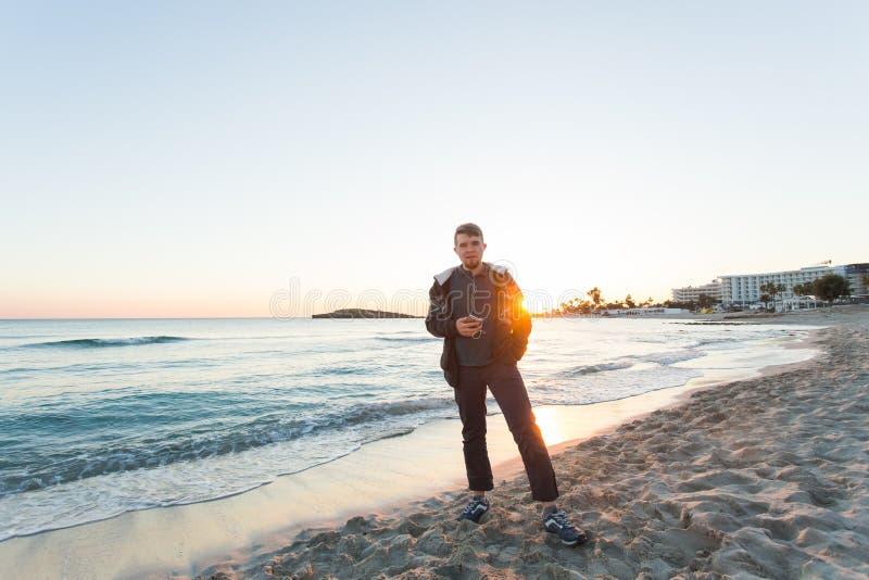 微笑和听到与海的音乐的年轻人背景的 旅行、假日、技术和人概念 免版税图库摄影