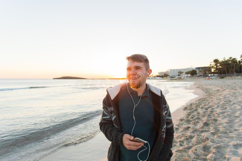微笑和听到与海的音乐的年轻人背景的 旅行、假日、技术和人概念 库存照片