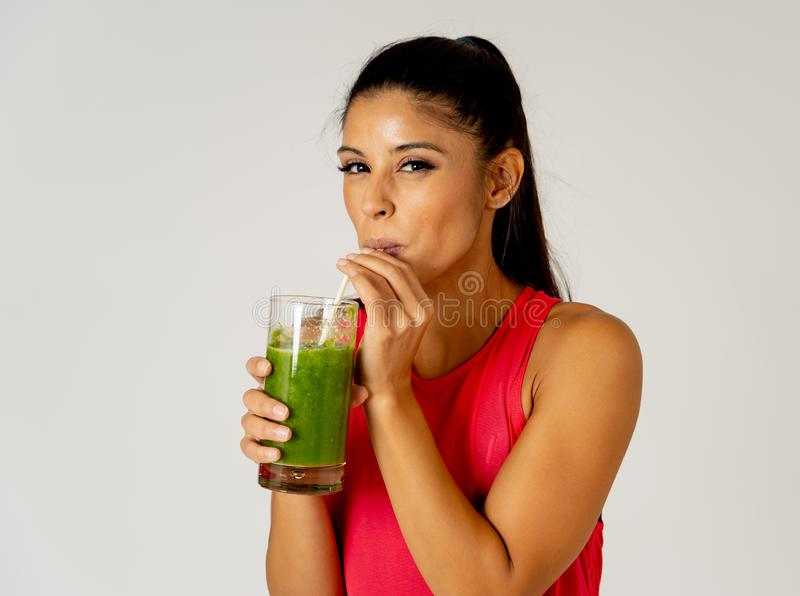 微笑和喝健康新鲜蔬菜圆滑的人的愉快的美丽的适合体育妇女 免版税库存图片
