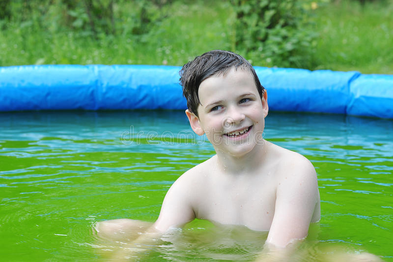 微笑和坐在水池的逗人喜爱的男孩 免版税库存照片