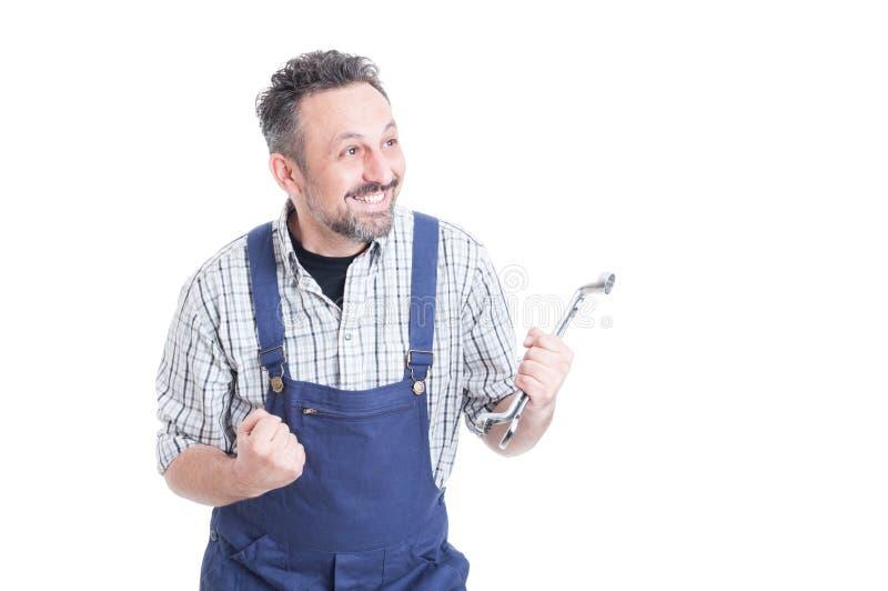 微笑和庆祝成功的快乐的英俊的技工 免版税库存照片