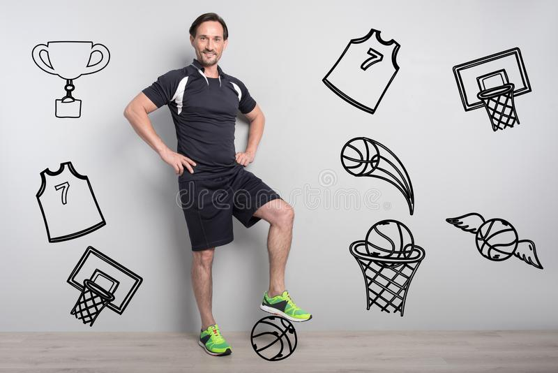 微笑和把他的脚放的成功的运动员在球上 免版税库存图片
