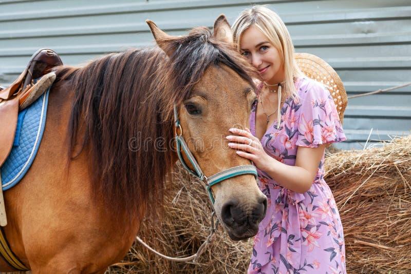 微笑和抚摸一匹棕色马的年轻女人在干草堆附近吃干草在一个夏天晴天的步行前 库存照片