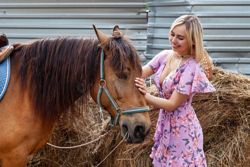 微笑和抚摸马的年轻白肤金发的妇女在干草堆附近吃干草在一个夏天晴天的步行前 免版税库存图片