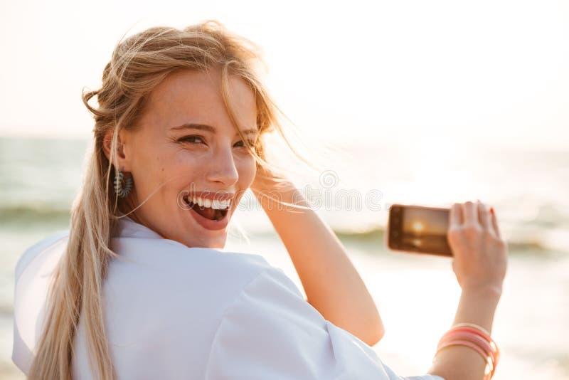 微笑和拍太阳的照片愉快的白肤金发的妇女20s照片  免版税库存图片