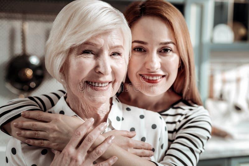 微笑和拥抱她年迈的母亲的平安的中间年迈的妇女 库存照片