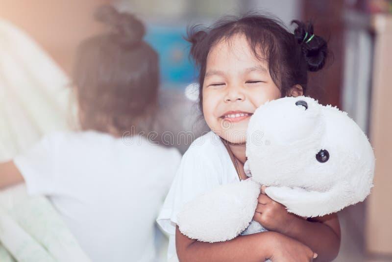 微笑和拥抱她的充满爱的愉快的亚裔儿童女孩玩偶 图库摄影