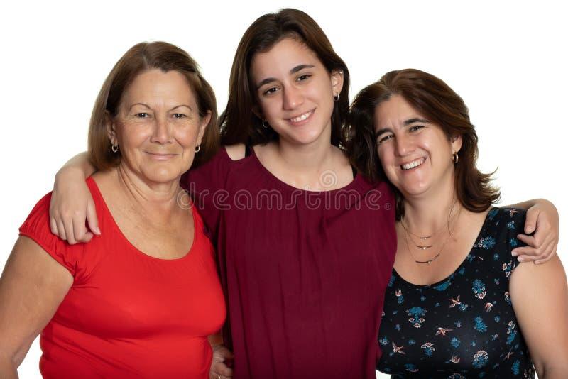 微笑和拥抱-在白色背景的拉丁妇女的三世代 免版税库存照片