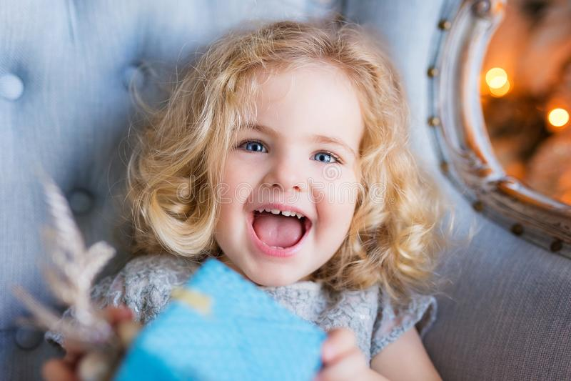 微笑和拿着一个当前箱子的美丽的愉快的小女孩 免版税库存图片