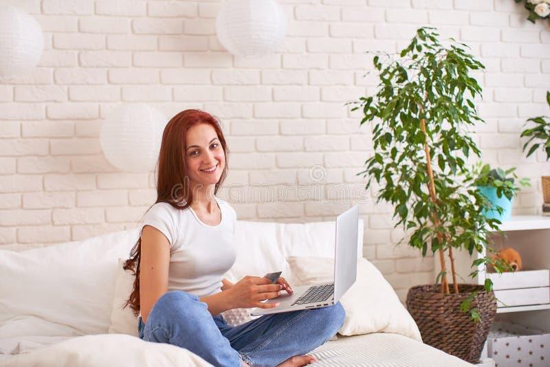 微笑和拿着一台万一银行卡和膝上型计算机在床上的美丽的少女 库存图片