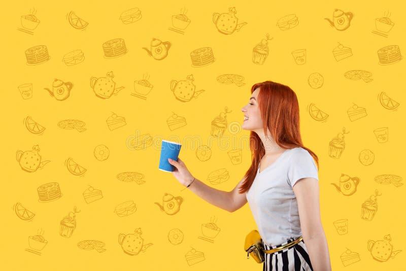 微笑和拿着一杯咖啡的愉快的女孩 库存照片