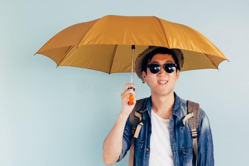微笑和拿着伞的年轻亚裔游人被隔绝在淡色蓝色背景 单独和正在寻找伙伴旅行 库存照片
