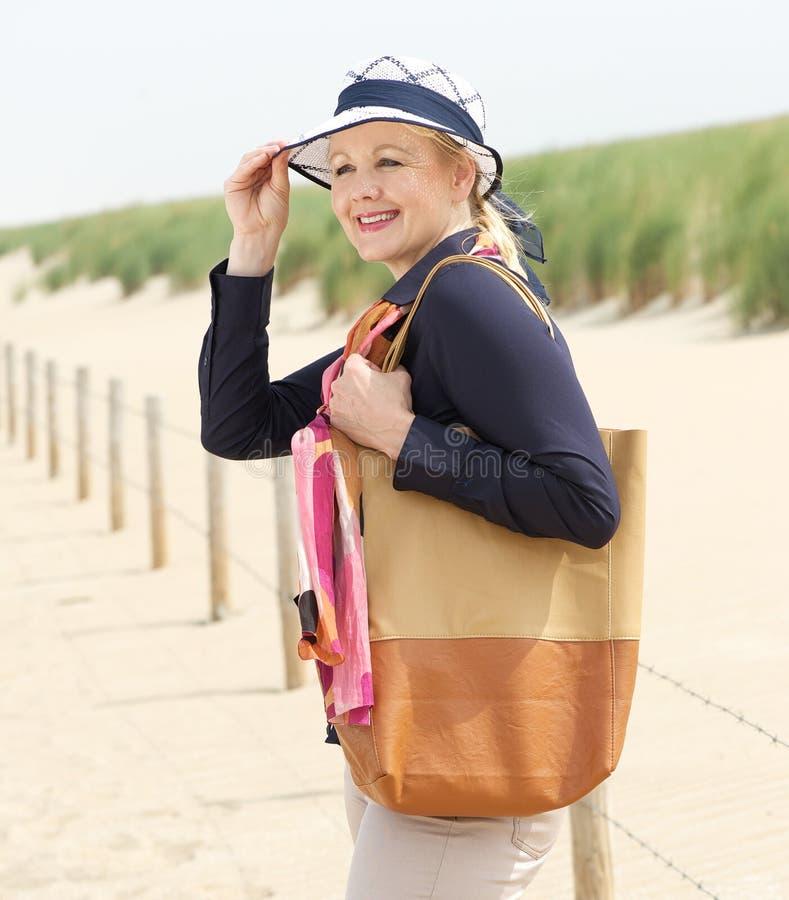微笑和拿着她的帽子的老妇人在海滩 免版税库存照片