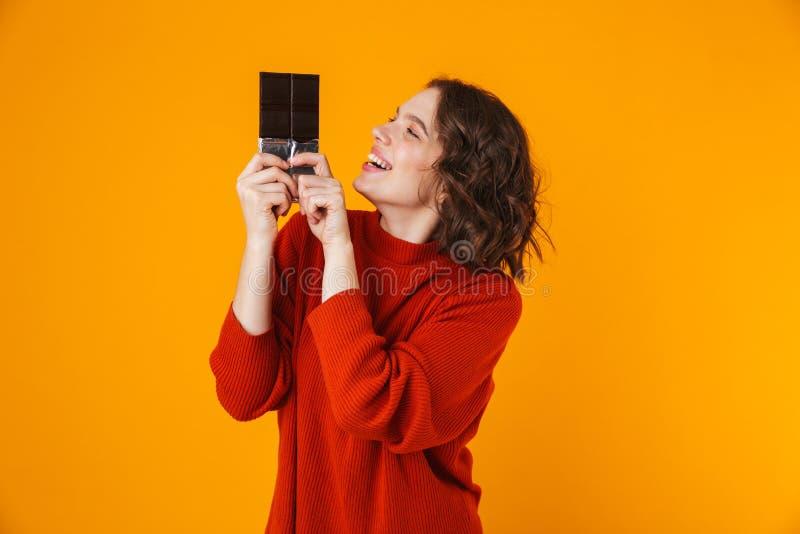 微笑和拿着巧克力块的欢悦妇女画象,当站立隔绝在黄色背景时 免版税库存图片