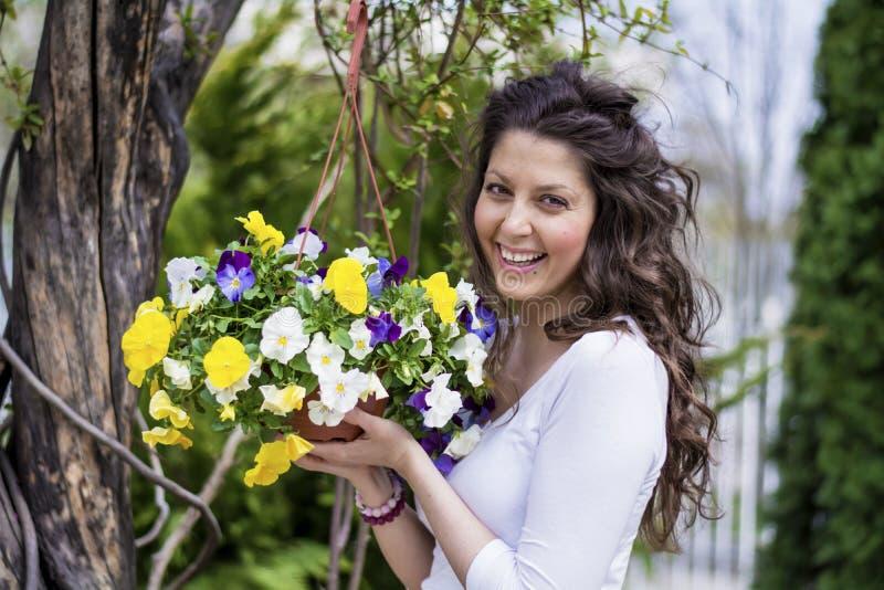 微笑和拿着春天的篮子美丽的深色的妇女开花 库存照片