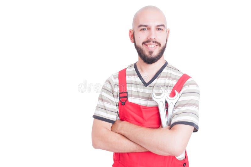 微笑和拿着板钳的友好的水管工或技工 免版税库存图片