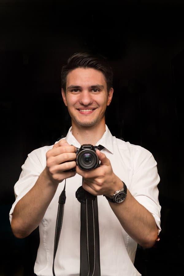 微笑和拿着照相机的美丽的年轻欧洲人 免版税图库摄影