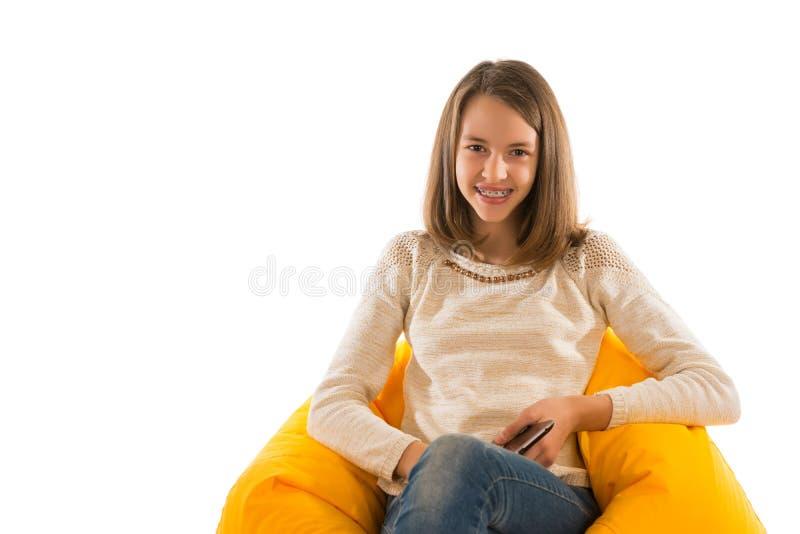 微笑和拿着片剂的年轻逗人喜爱的女孩,当坐时 免版税库存图片